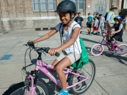 Girl with helmet riding bike near school.