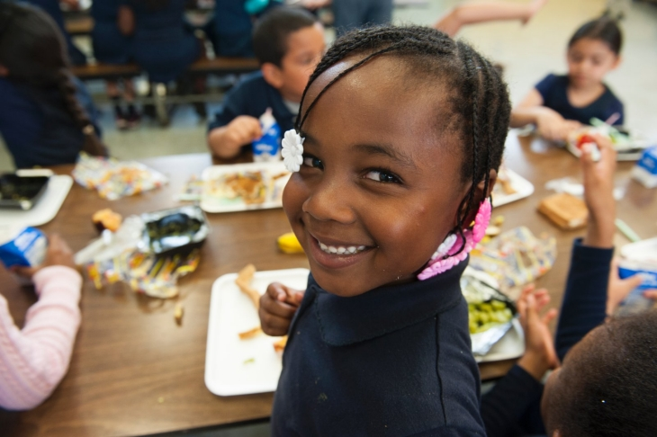 Young girl smiles at camera while eating lunch