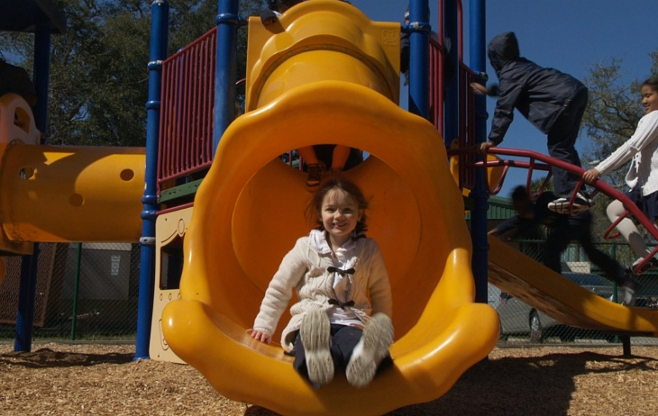 A girl pictured at the bottom of a playground slide.