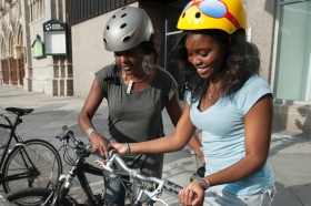 Two women with helmets removing their bikes from a street bike rack.