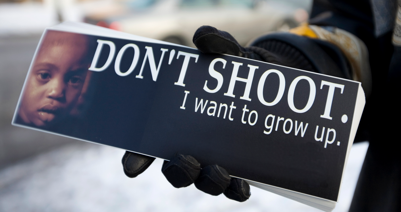 "A Cease Fire volunteer in Chicago hands out bumper stickers that read, ""Don't Shoot. I want to grow up."""