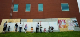 A group painting a mural on the side of a building.
