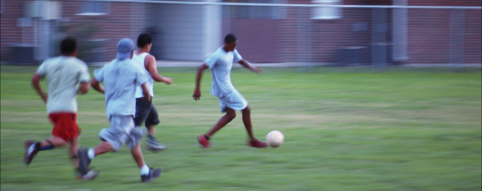 A group of teens playing soccer.