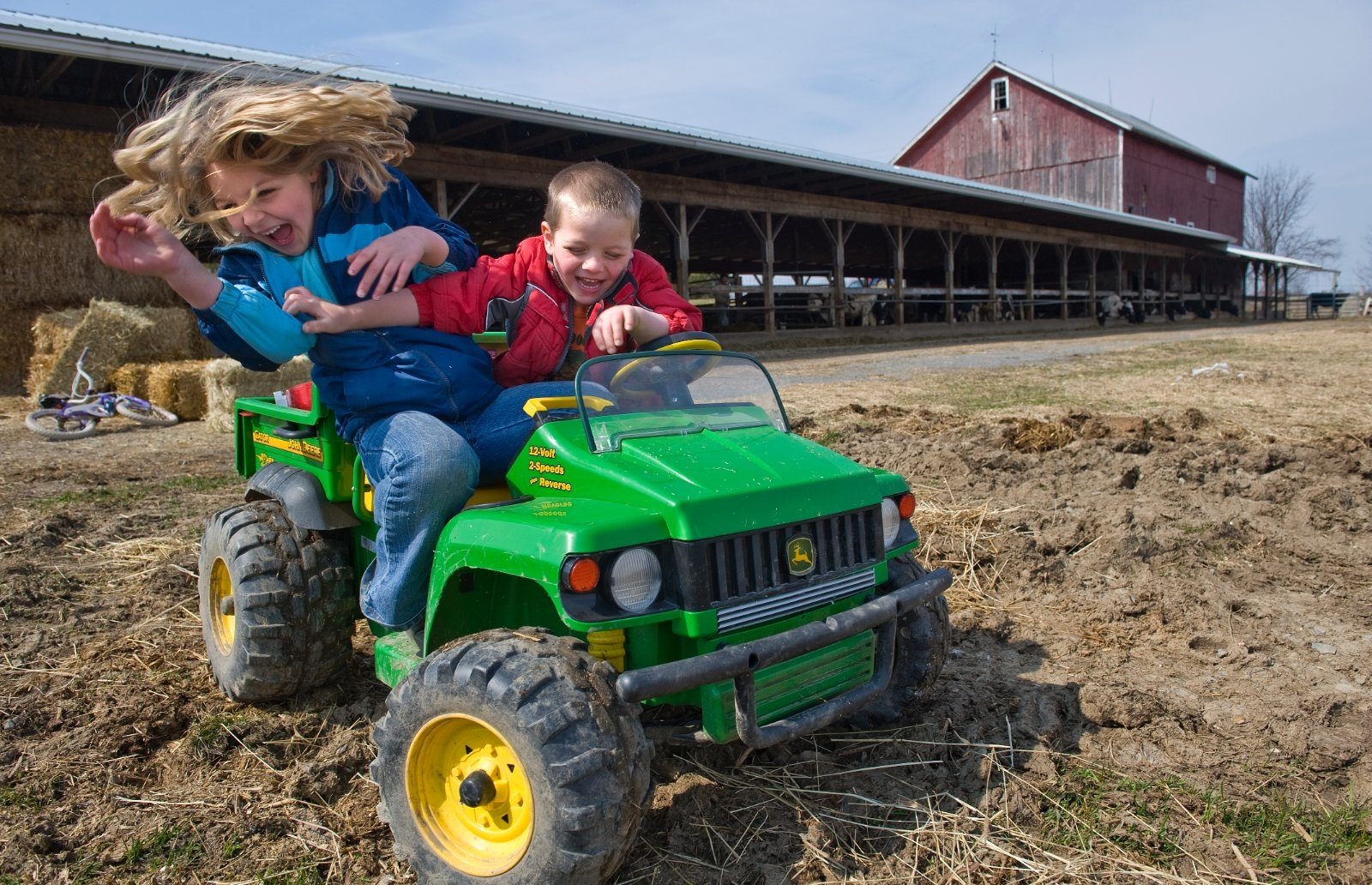 Two children play in a toy tractor on a farm.