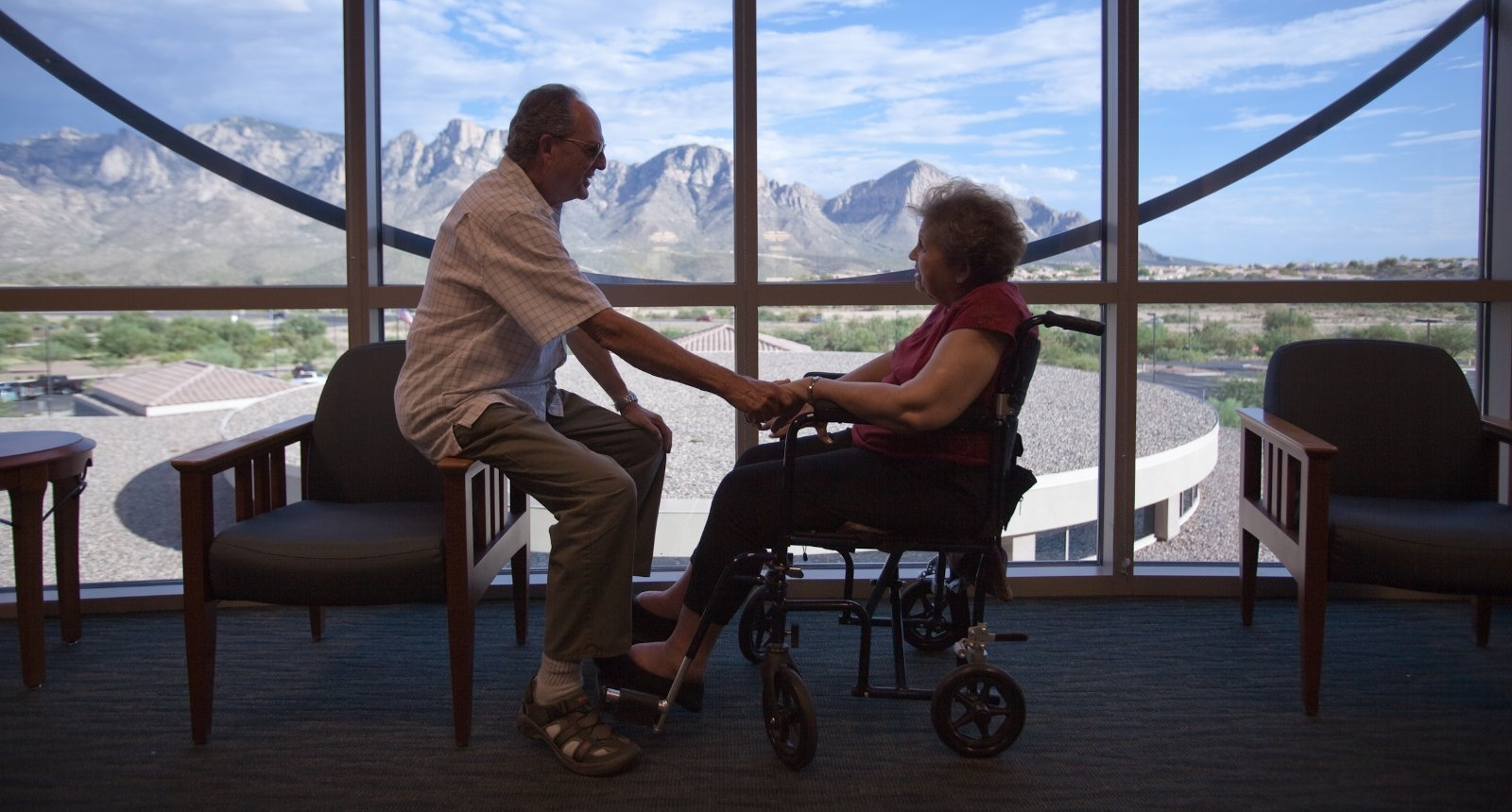 An elderly couple, the woman in a wheelchair sitting in front of a large window showing a view of mountains.