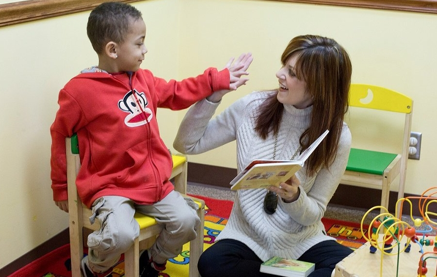 Adult and child reading a book in the classroom.