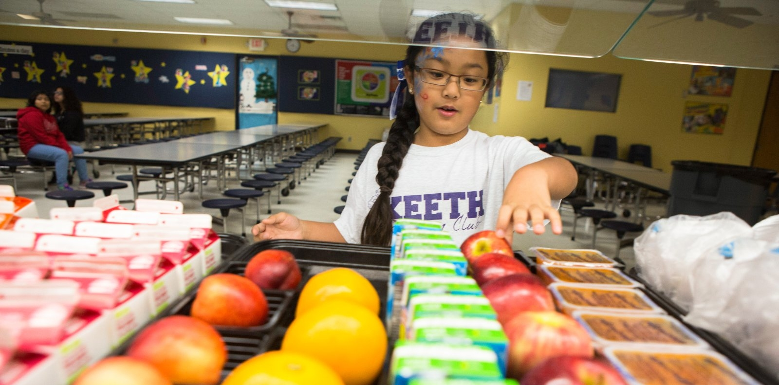 A girl selects a healthy snack in a school cafeteria.