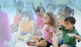 Children raise their hands in a classroom.