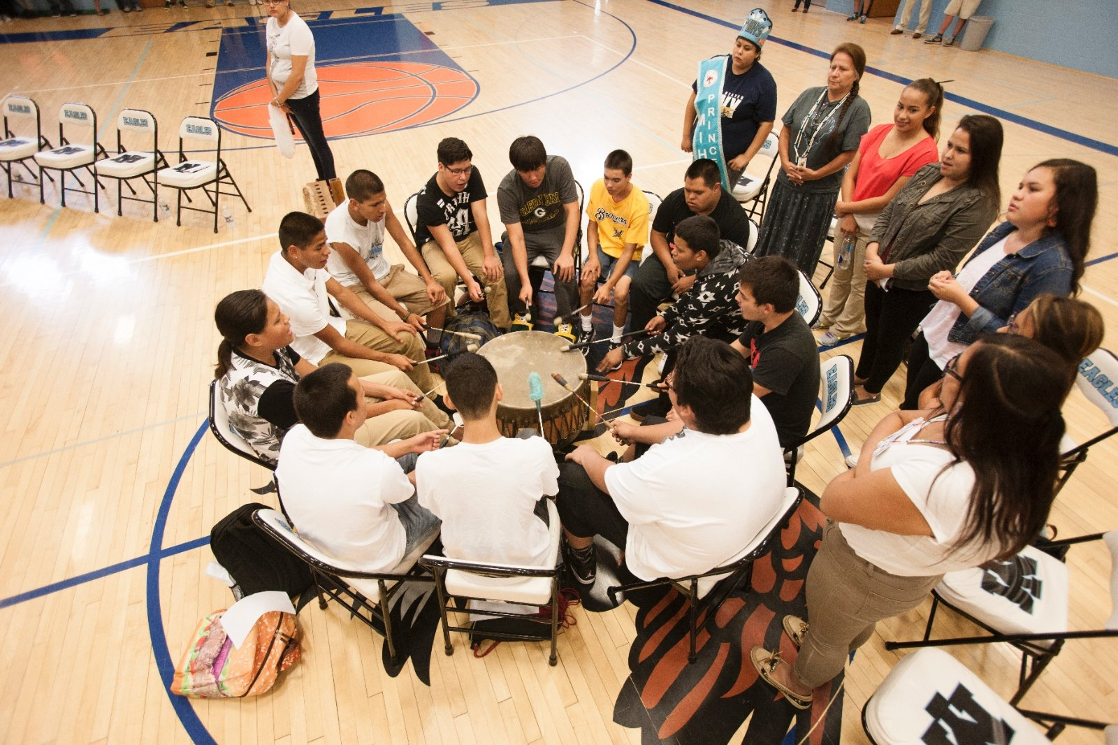 Students chant and play the drum during a welcome ceremony.