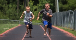 Two boys running on track.