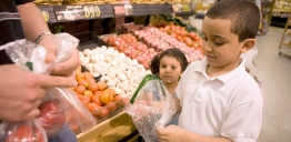 A boy helps his father select salad from a supermarket produce section.