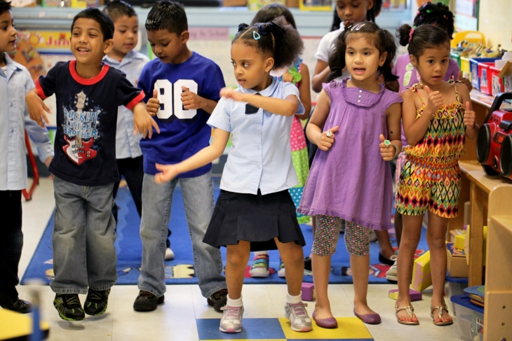 A group of students dance in a classroom.