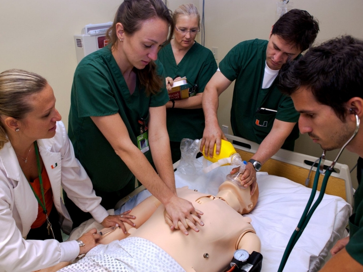 Nursing students working on a mannequin during a class.