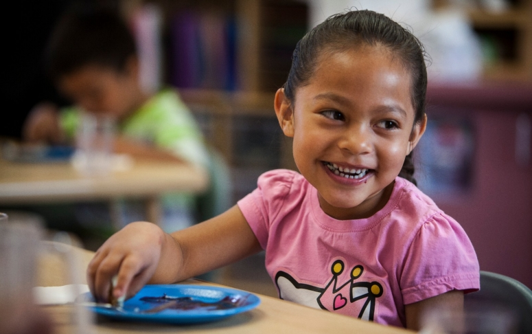 A girl smiles as she eats a healthy snack at school.