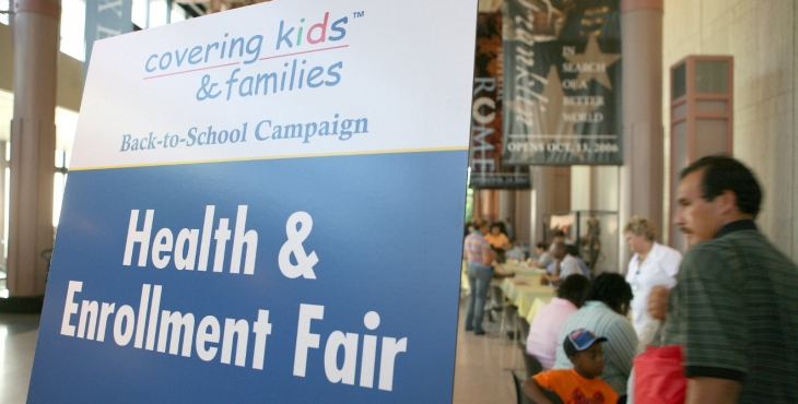 Attendees visit tables at a health and enrollment fair.