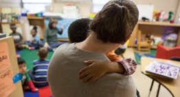 Teacher holds a student during class.