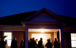 Neighbors gather around a home at night.