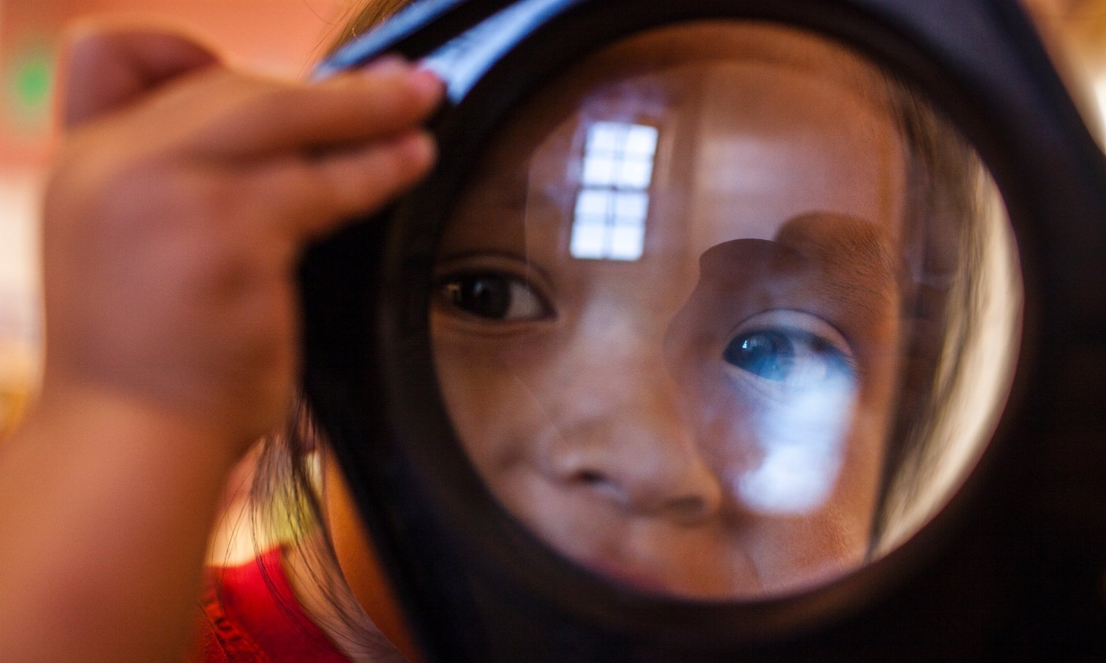 A child looks through a large magnifying glass.