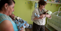 A doctor holds an infant during a home visit.