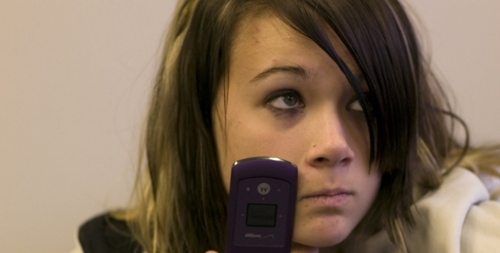 A teenage girl resting her cell phone against her face.