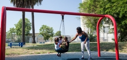 Mother pushes kids on a tire swing.