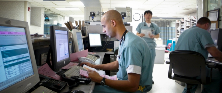 Health professional in a hospital typing patient information into a computer.
