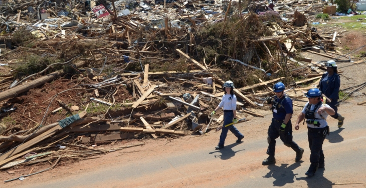 Relief workers walking past rubble after a tornado.
