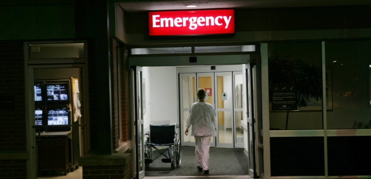 A nurse enters a hospital through the Emergency entrance.