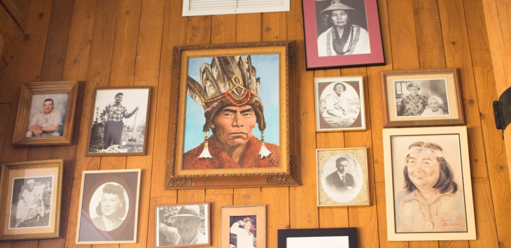 Wood paneled wall with Native American portraits.