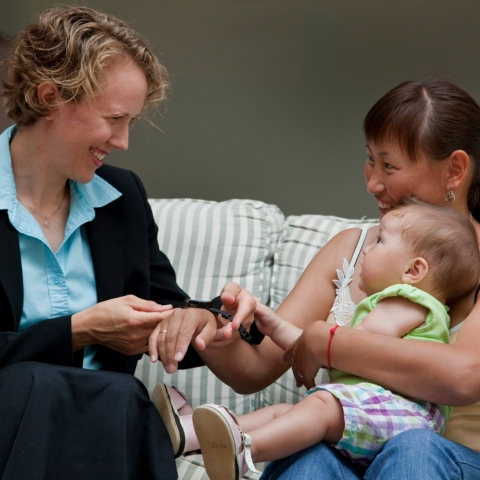 Caseworker sits with mother and baby on a couch.