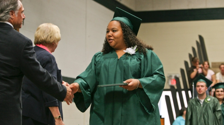 A young woman receives a diploma at her graduation ceremony.