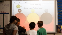 Students use an interactive screen to communicate feelings.