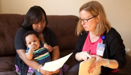 A mother and her son meet with a care coordinator.
