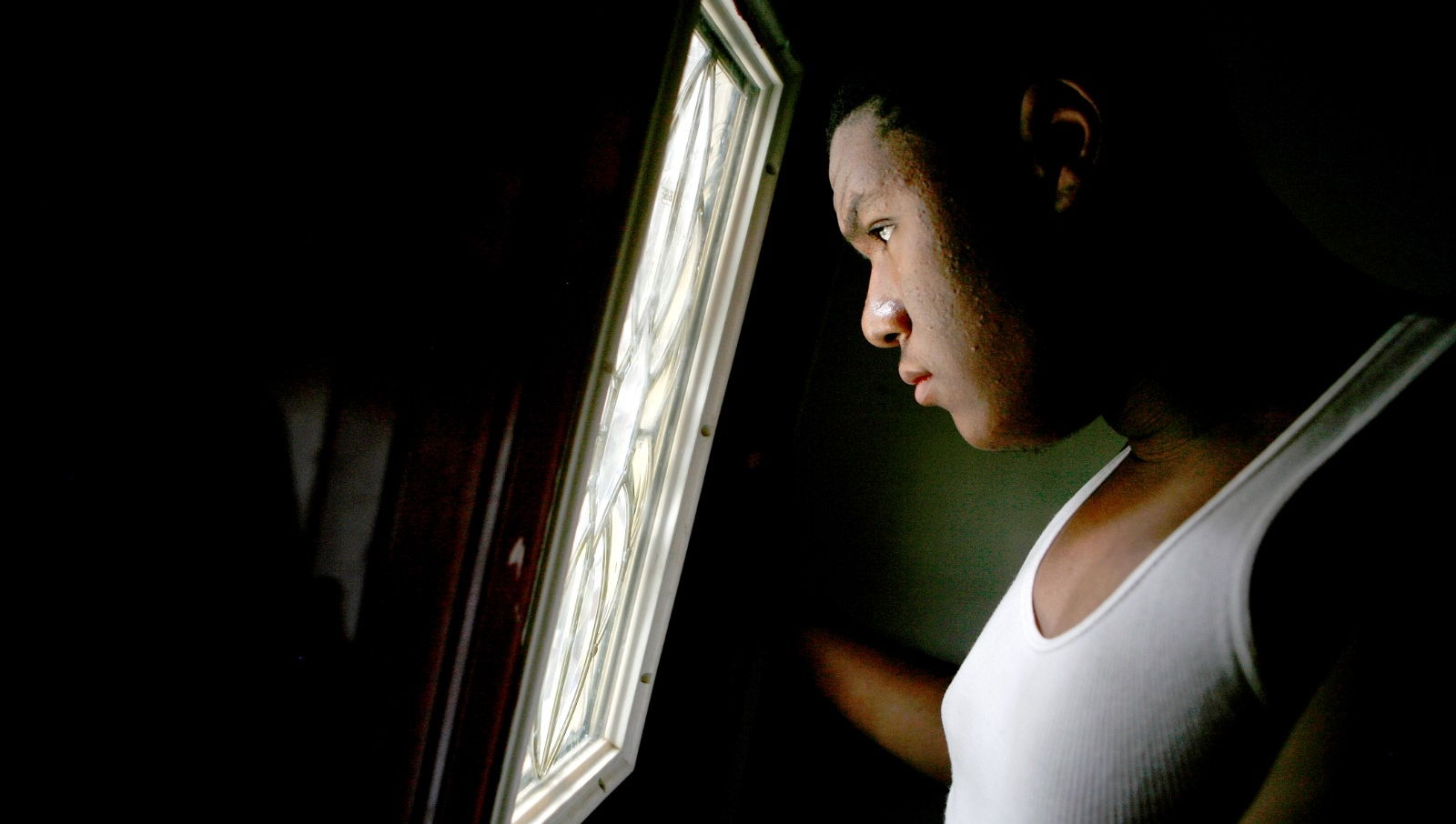 A teenage boy looks out of a window.