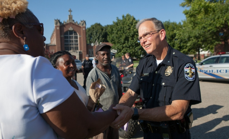 Police officer shakes hands with smiling citizens.