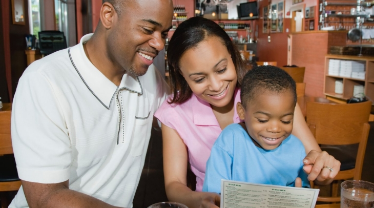 A family reading a menu in a restaurant.