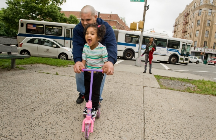 A father rides with his young daughter on a pink scooter.
