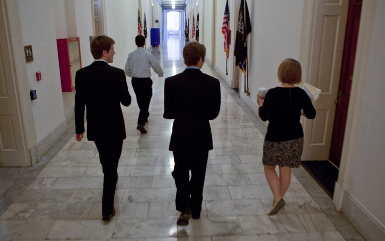 People walking in a hallway of a government building.