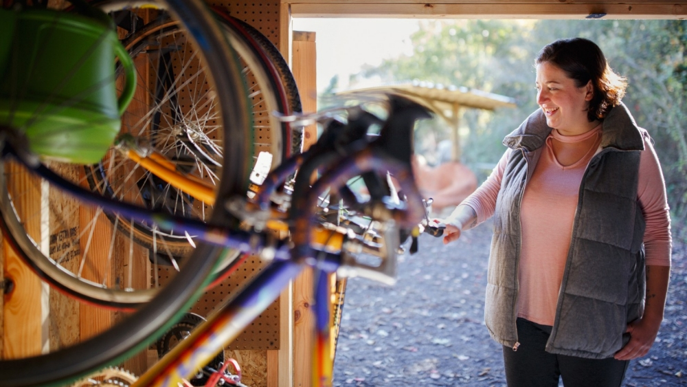 Health Advocate Emily Shock shows bicycles available for patients at The Free Clinics.