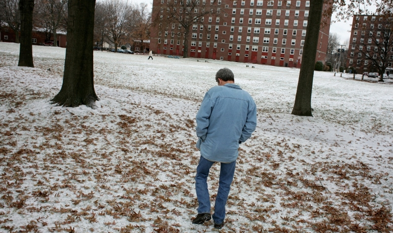 A man walks over a snow covered lawn.