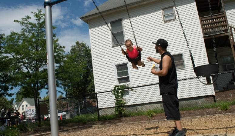 A father and daughter play on a  swingset.
