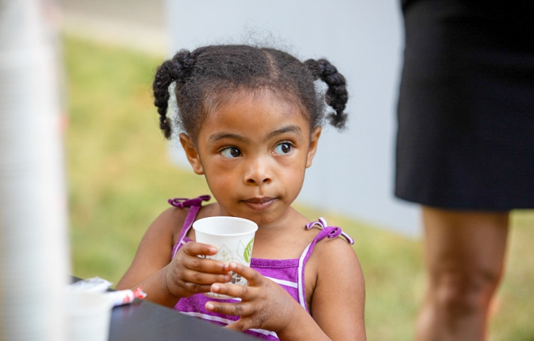 Young girl drinking from a cup.