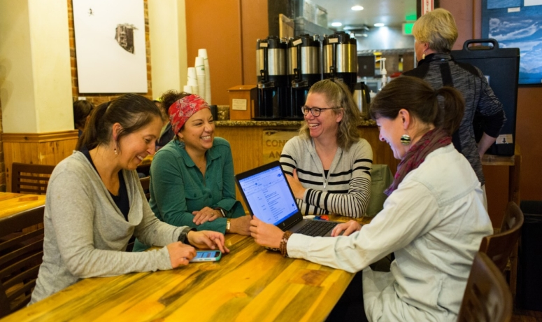 Four women laugh around a table in a coffee shop.