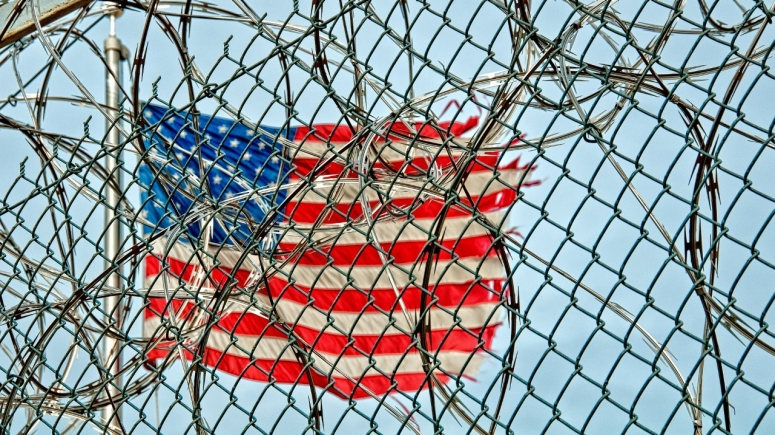 American flag behind barbed wire fence.