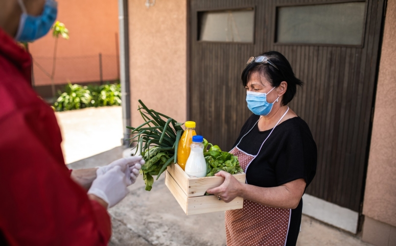 Woman wearing protective mask taking groceries from caring volunteer.