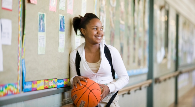 A smiling student holds a basketball while standing in a school hallway.
