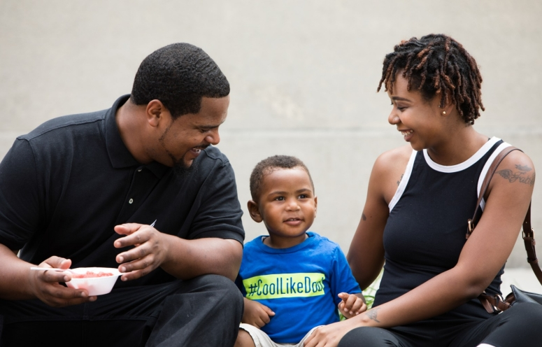 A smiling family shares a moment together during a summer event.