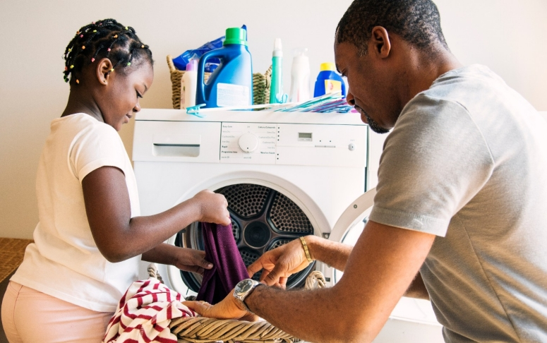 Father and daughter do laundry together.
