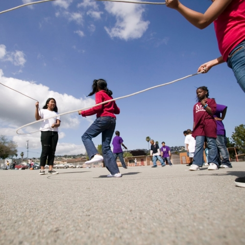 Students play jump rope in a school playground.