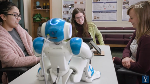 Three woman interact with a robot in a lab.